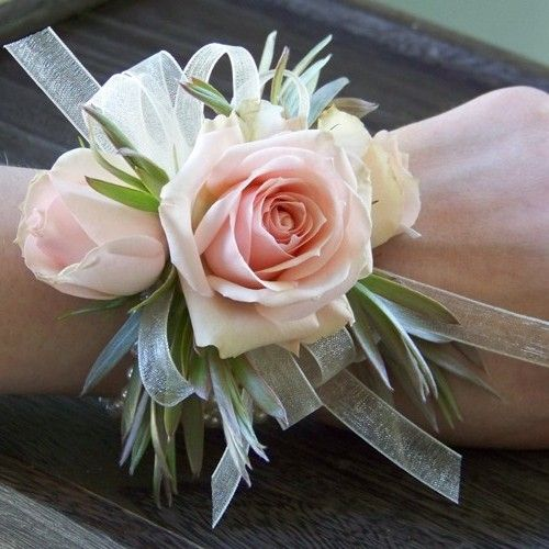 wrist corsage with Star Blush spray roses, green leucadendron and ivory chiffon ribbon on an ivory pearl bracelet