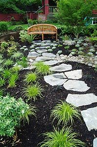 Basalt stepping stones cross a dry stream bed that mitigates a disconnected downspout. VIEW: A restful spot awaits.