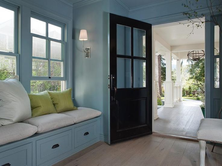 A+black+and+blue+front+door+opens+to+a+blue+mudroom+filled+with+a+blue+built-in+bench+window+seat+adorned+with+bronze+cup+pulls+lined+with+heather+gray+cushions+and+lime+green+linen+pillows.