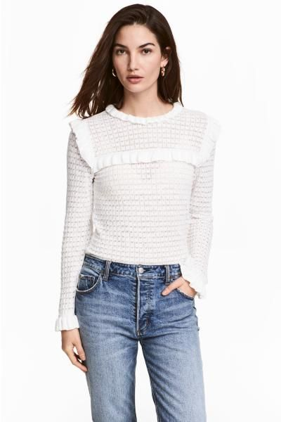 Jumper knitted in a fine, textured cotton blend with a frilled collar, opening with a button at the back of the neck and frill trims at the yoke, shoulders