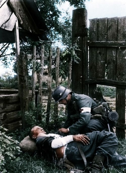 On the Soviet front: A German medic gives on the spot first aid assistance to a wounded Kamerad.      Army Group South, Ukraine, August 1941.