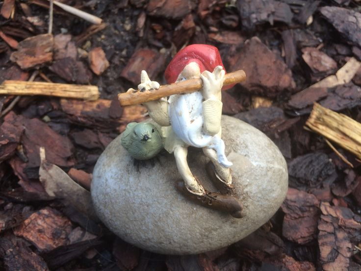 Garden gnome sitting on a rock playing flute with a bird
