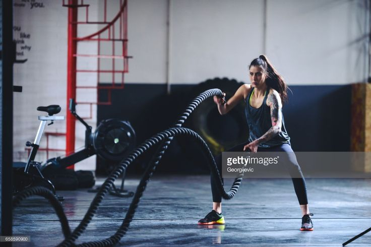Woman working out with heavy ropes in the gym.
