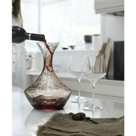 Decanting of wine into a carafe unfolds the full potential of the wine, but also elevates a young everyday wine to a more interesting taste experience.When you pour the wine along the narrow neck of the carafe, the wine is flung around by the centrifugal force and is deposited in a millimetre-thin layer on the inside of the carafe for efficient oxidisation. #holmegaard #perfection #carafe