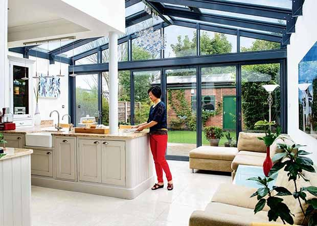 A glazed extension Below: A dramatic three-storey glazed timber extension has transformed this 1920s detached home, which now features a colourful, open-plan layout.