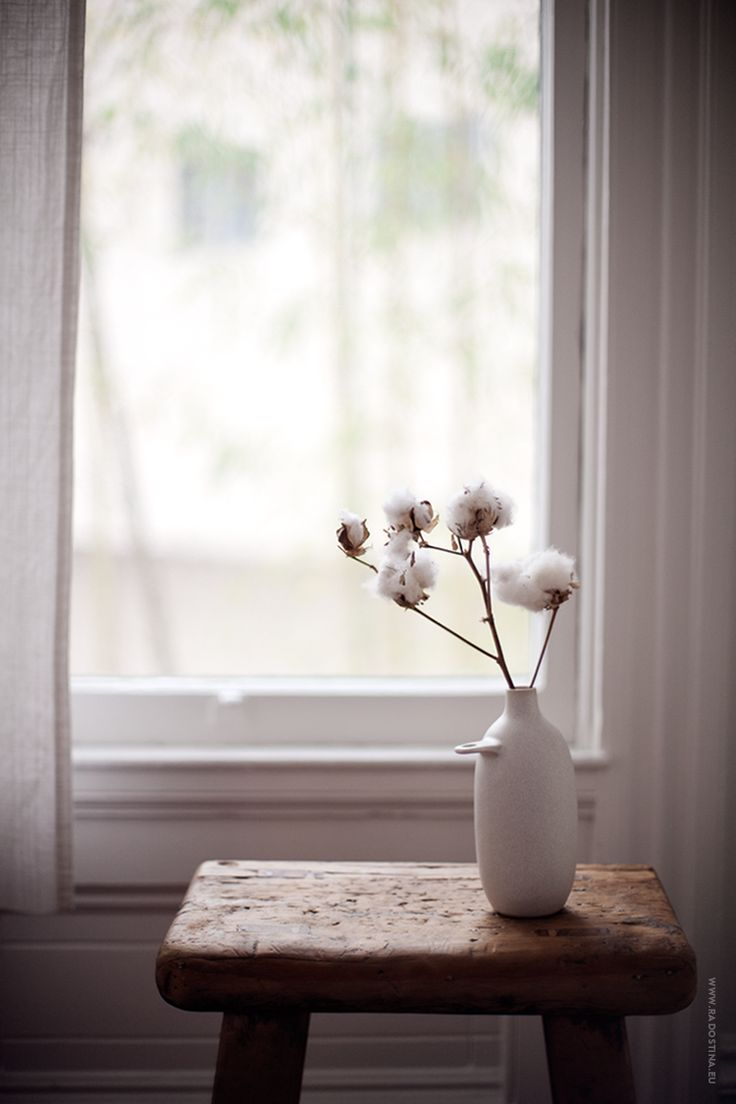 twigs with raw cotton buds displayed in a ceramic vase on a timber stool   #wabisabi