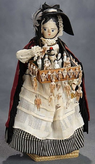 """10"""" (25 cm.) The carved wooden doll with painted black hair and facial features, large blue eyes, defined nose, jointing at shoulders, elbows, hips and knees, wearing antique peddler costume. Condition: generally excellent, glass dome is repaired. Comments: Grodnertal, circa 1880. Value Points: the peddler lady holds a wooden tray that offers more than 35 tiny porcelain and wooden dolls; the doll is preserved on wooden base under glass dome."""