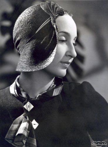Onbekend | Damesmode, hoeden. A-symmetrische strohoed waarvan de brede rand aan de  voorkant geplooid en teruggeslagen is en versierd met een hoedenspeld. Zonder  plaats, 1934.
