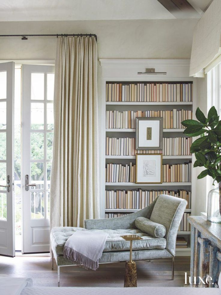 A chaise lounge is the perfect spot to read, especially when you are surrounded by an in-home library.