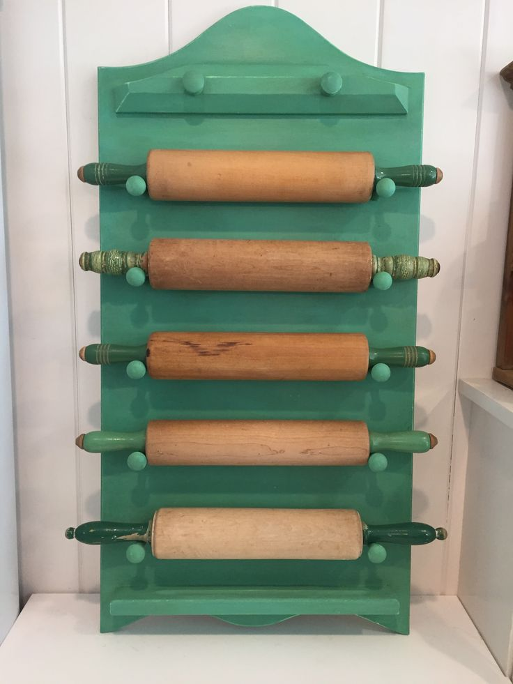 Vintage rolling pin holder made with a repurposed garage sale children's memo board.  I added coat hooks & painted the memo board with Annie Sloan chalk paint to display five green-handled rolling pins from my collection.  Photo by : Leslie Guerci.