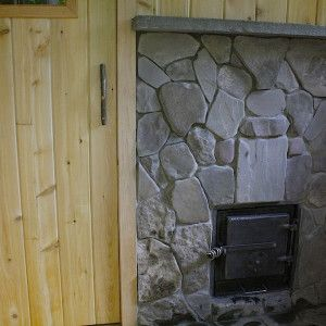 custom sauna stove by Rob Licht Custom Saunas set in stone faced wall using stones from the property