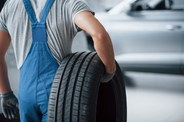 Download Repair Concept Mechanic Holding A Tire At The Repair Garage Replacement Of Winter And Summer Tires For Free Garage Repair Repair Tire Repair