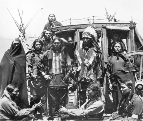 Albert Afraid-of-Hawk and eleven other Sioux men in front of a stagecoach