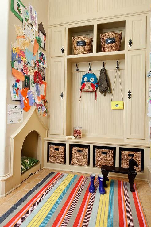 Kid and pet friendly mudroom is fitted with a cream built-in dog house fixed beneath a children's art wall and adjacent to a cream beadboard mudroom cabinets built in on either side of overhead shelves holding labeled woven baskets over oil rubbed bronze coat hooks.