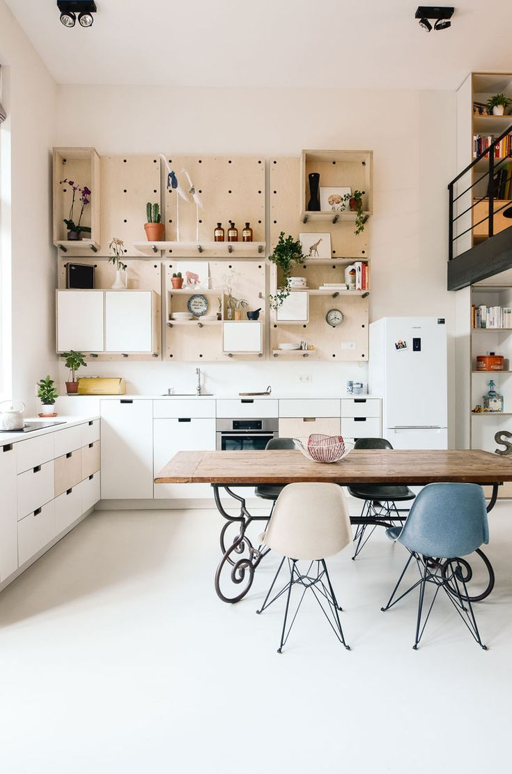 Kitchen: white and wood cabinetry with cut-out handles, white floor, wooden dining table on curved metal frame, Eames multicoloured shell chairs with black Eiffel base, plywood open shelving with asymmetrical cabinets, indoor plants, cactuses