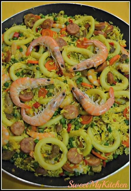 Arroz à Valenciana  Ingredientes: 1 embalagem de Camarão  Azeite q.b. 1 cebola grande picada 2 dentes de alho picados 1 embalagem de Argolas do Mar  150g salsichas de churrasco, às rodelas 3 cenouras grandes, às rodelas 300g ervilhas 1 pimento verde pequeno picado 1 pimento vermelho picado 250g miolo de ameijoa 300g bifanas de porco, em pedaços 400g arroz Agulha Bom Sucesso 800g a 1000g água da cozedura dos camarões Fios de açafrão q.b. Sal q.b. Flocos de malagueta q.b. Preparação: - Comece…