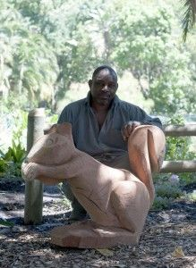 Godfrey Chimhanzi, with his squirrel sculpture carved from a repurposed tree trunk outside The Company Gardens Restaurant Cape Town | bthings.me