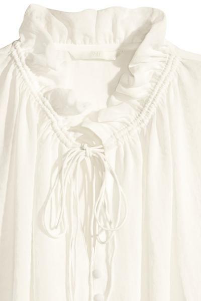 Blusa de manga larga en tejido vaporoso con cuello con pequeños volantes y cordón de ajuste, botones revestidos en la parte superior, y puños y parte inferi