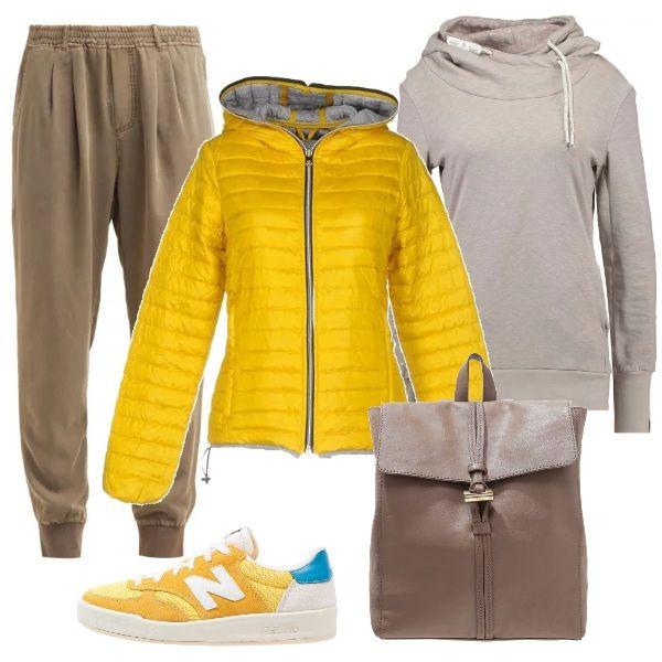 Lo splendido piumino giallo di Duvetica è abbinato a pantaloni in viscosa, vita alta stretti alla caviglia, felpa di cotone con cappuccio, sneakers New Balance gialle e zainetto di pelle.
