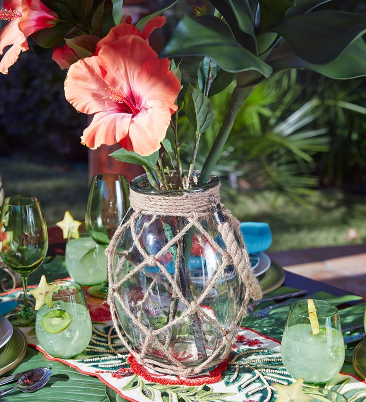 Table centerpiece with a rope net jar vase: http://www.completely-coastal.com/2016/05/5-coastal-nautical-theme-table-settings.html A colorful tropical theme table setting!