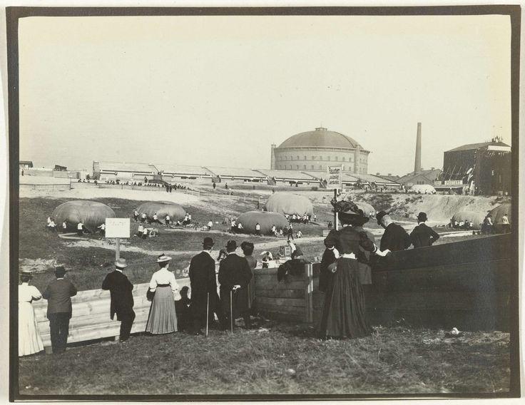 Anonymous | De derde Gordon Bennett ballon race, Anonymous, 1908 | Op de grond een stuk of zeven ballons die opgeblazen worden, met mensen eromheen. Op de voorgrond publiek. Op de achtergrond de gebouwen van de gasfabriek in Schwargendorf.