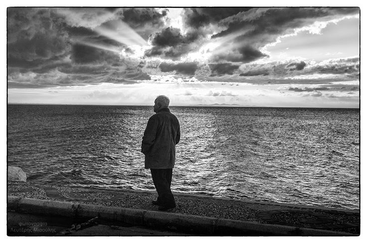 Old man across sunset in Patras