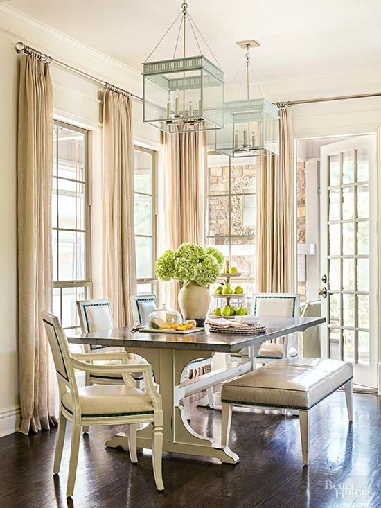 A hand-distressed finish on the base of a made-to-measure breakfast table camouflages scrapes and scuffs. The furniture's antique styling is juxtaposed with the modern scale of slate blue iron lanterns./