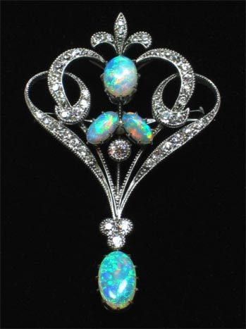 An Edwardian Brooch with four opal stones and an array of diamonds set in 18ct white gold.