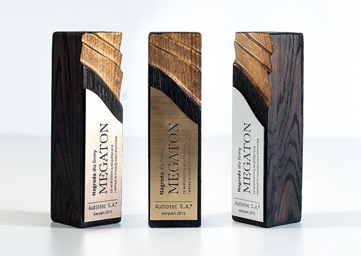 Nowoczesne statuetki dla firmy Megaton.Wykonane z ręcznie żłobionego drewna i nowoczesnego laminatu grawerskiego w trzech kolorach – brązowym, srebrnym i złotym.