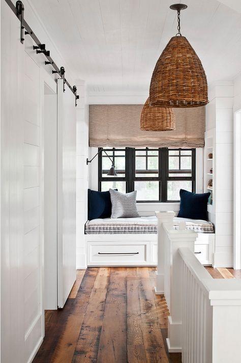 Farmhouse landing with shiplap, window seat reading nook, barn door, and rustic wide plank hardwood floor. Jennifer Worts Design Inc