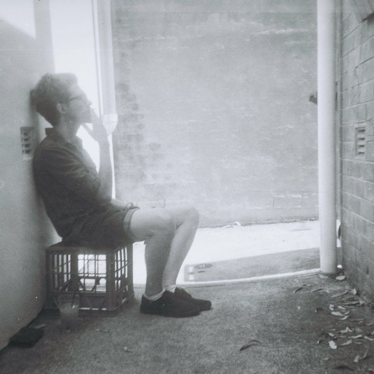 Film photo. Guy sitting on a crate, on his work break. Photo by Jo Willowtails. Taken on instamatic 33 with film that expired in 1974.