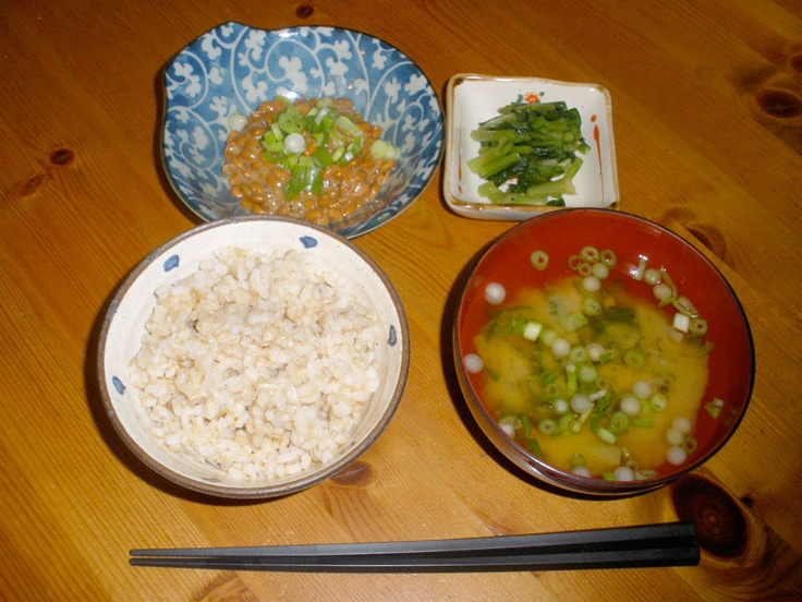 Typical Japanese style breakfast with rice, miso soup, natto, and pickles.