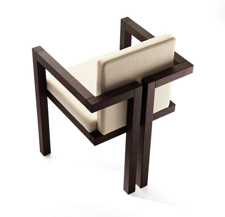 Projeto da cadeira de madeira com braços, design por Alberto Collovati. Uma cadeira de caráter intenso e habitual, que é reforçada pelo assento de couro e encosto, para não mencionar o recurso armrests. Destaca-se a continuidade simétrica do design, particularmente evidente quando se olha para a parte de trás da mesma. Duas pequenas gavetas laterais extraíveis contribuem para a sua singularidade.