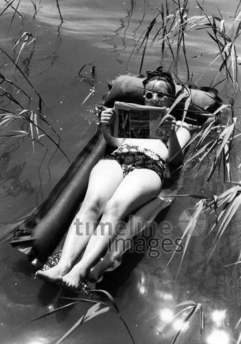 Frau auf einer Luftmatratze im Wasser ullstein bild - ullstein bild/Timeline Images #Luftmatratze #Frau #Baden #lesen #Zeitung #Sonne #Sommer #historisch #Freizeit #schwarz-weiß #Badeanzug #Urlaub #See
