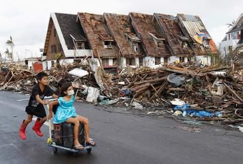 Children pass by debris and damaged houses as they look for water in typhoon-devastated Tacloban City on Wednesday, November 13. Philippine officials have been overwhelmed by Yolanda, one of the strongest typhoons on record, which tore through central Philippines on November 8 and flattened Tacloban and other towns along its path. Officials fear thousands may have died, many drowning in a tsunami-like wall of seawater.