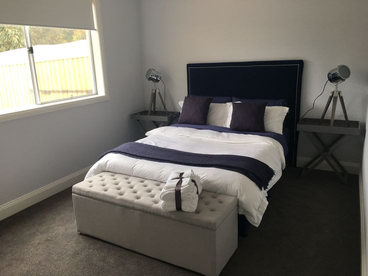 Guest double bedroom with handmade upholstered headboard in navy velvet. Crisp white linen and blanket box.
