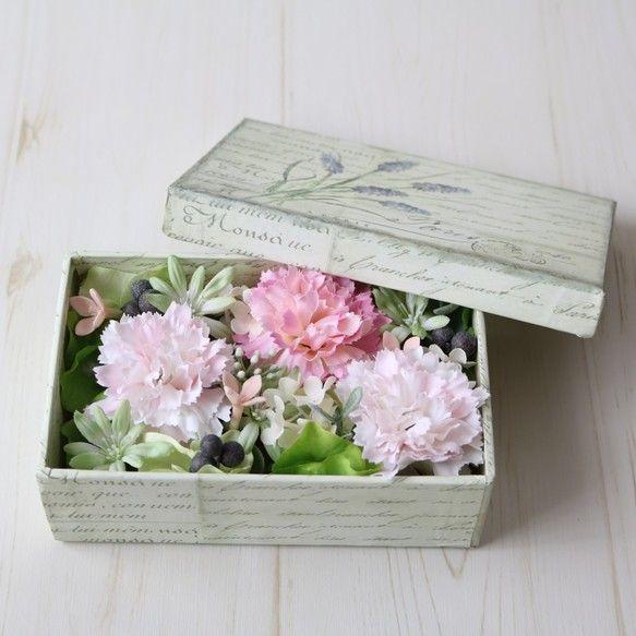 ◆ story ◆お母さんに日頃の感謝を伝える母の日に、可愛いお花を贈りたいとお探しの方も多いのではないでしょうか。ふわっとした色合いがお好きなお母さん、優しい雰囲気のお母さんをイメージして、ムスカリが描かれたフレンチアンティーク調のスクエアBOXに、カーネーションや小花、実ものをアレンジしました。プリザーブドフラワーではなく全てアーティフィシャルフラワーなので、蓋を開けたまま長く飾っていただけるのも嬉しいポイントです!◆ point ◆受注制作とさせて頂いておりますので、1週間ほど制作にお時間を頂いております。お急ぎの場合は極力対応させていただきますのでお問い合わせください。◆ photo ◆ ① 全体のバランスを大切にしました。②黒いベリーがポイントで引き締め役を♪③ふたの模様もとっても可愛らしいです。④透明なセロハンでラッピングし、リボンをつけてお届けいたします。◆ materials ◆ ペーパーボックスアーティフィシャルフラワー ・カーネーション・あじさい・ブバリア・スノーボール・ユーカリ・ベリー◆ size ◆横16cm×縦10cm×高さ6cm(ふた装着時)