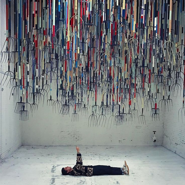 simon birch the crusher pitchfork installation exhibition art - 300 painted pitchforks hanging from the ceiling.  The artist want people to spend time under them looking up ay the art. Would you dare?