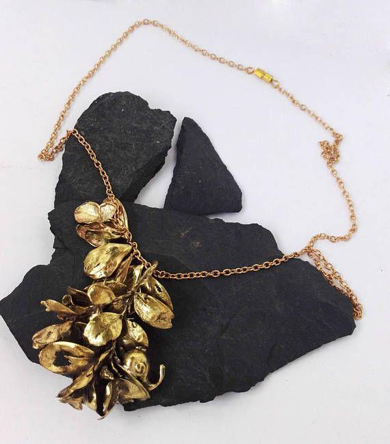 Este sobrio y original colgante dorado se compone de una cadena decorada con hojas fundidas del natural, rematado en un llamativo colgante a juego. Entre las ramas y hojas, repta un pequeño y adorable caracol. Los amantes de la naturaleza lo adorarán