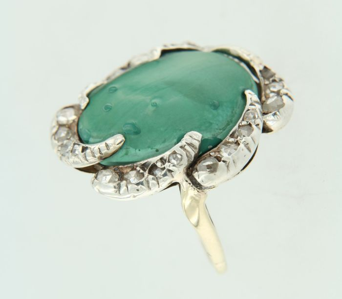 18k en Z1 zilver met gouden ring bezet met centraal een malachiet en roos geslepen diamanten  de bovenkant van de ring is 23 cm breed gewicht : 84 gr gezet met - 1 x 17 cm x 15 cm ovaal cabuchon geslepen malachiet Edelstenen zijn vaak behandeld om kleur of helderheid te verbeteren. Dit is niet onderzocht bij dit specifieke object - 14 x 10 mm - 25 mm roos geslepen diamant 020 caraatkleur : Wesselton zuiverheid : SI 18k en Z1 gekeurd door Waarborg Hollandring verkeert in goede staatWordt…