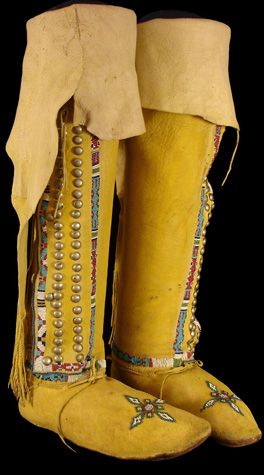 """Kiowa High-top Moccasins, 1880 The high-tops consist of supple, ochre-dyed hide. Single lanes of beadwork accent the shin covers, the vamps and the ankle seams. The designs are predominently geometric, consisting of designs which sit on alternating fields of white, blue and crimson. Running up the length of each shin guard are two rows of brass tacks; 17 1/2"""" tall and 9 1/2"""" long."""