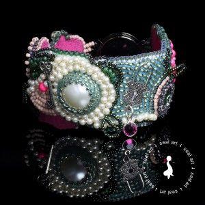 Przepiękna, bajkowa, misternie dopracowana w każdym szczególe bransoleta. Wykonana w technice 'Bead Embroidery'. Ozdobiona kryształowymi kaboszonami Swarovski oraz perłowym kaboszonem Swarovski i perełkami Swarovski. Całości dopełniają fantazyjne zdobienia w kolorze srebrnym. Wykonana na specjalnym podkładzie, została podszyta miękkim materiałem Super Suede w kolorze fuksji. Idealny prezent na każdą okazję: urodziny, imieniny, walentynki, pod choinkę.
