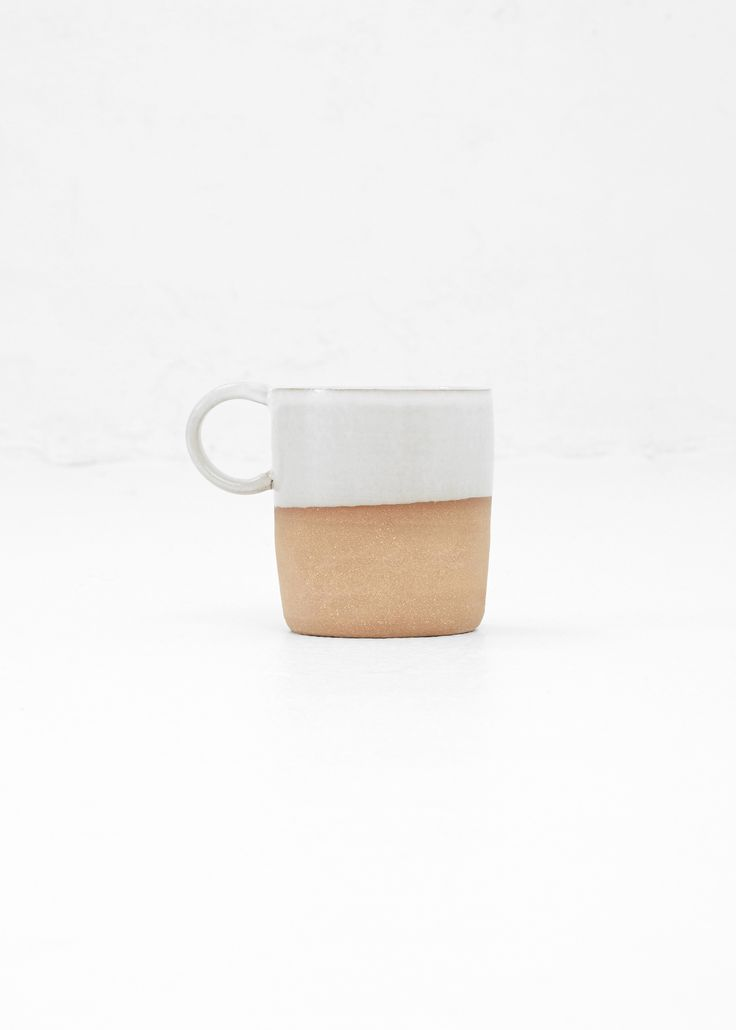 Helen Levi Camp Mug (Brown / White)Mug with a small, circular handle in raw tobacco clay halfway dipped at top in a white glaze. Inspired by enamel camping ware. Handle large enough to fit two fingers. Glaze level unique to each piece. Hand wash. Ceramic. Made in the USA.
