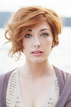 Short Wavy Hairstyles: The platinum short curly hairstyle is style casually. The bouncy curls make the whole look full of volume and movement. some blunt cut side sweeping bangs are layered subtly across the forehead to make the whole hairstyle look tender and soft.