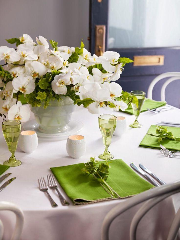 table ronde avec orchidées blanches, serviettes et verres verts