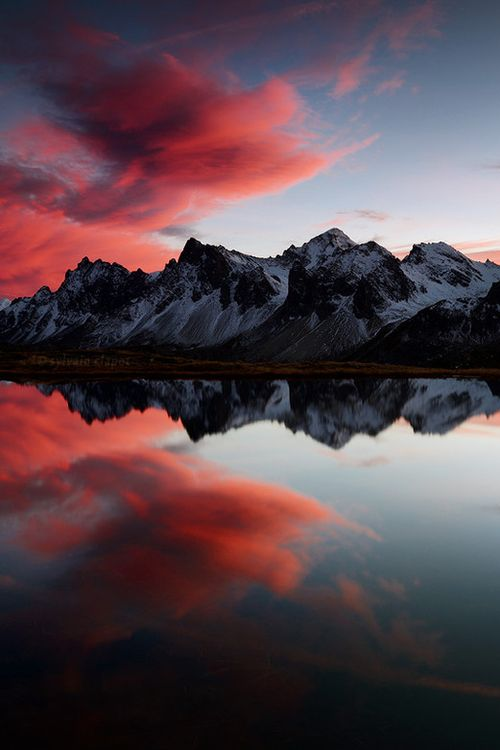 Reflection. Gorgeous photograph of the mountains, water and setting sky.