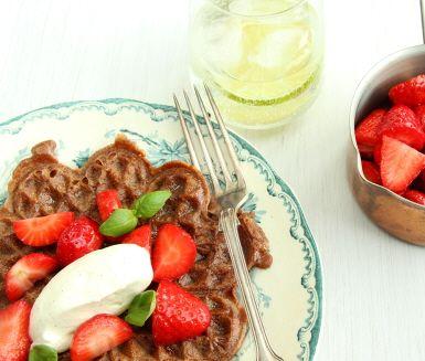 Chokladvåffla med jordgubbskompott är ett roligt alternativ till den klassiska frasvåfflan. Kakao och vit choklad blandas i smeten och tillsammans med den vaniljsmakande grädden blir det ett härligt fika till våffeldagen. Garnera gärna med basilikablad.
