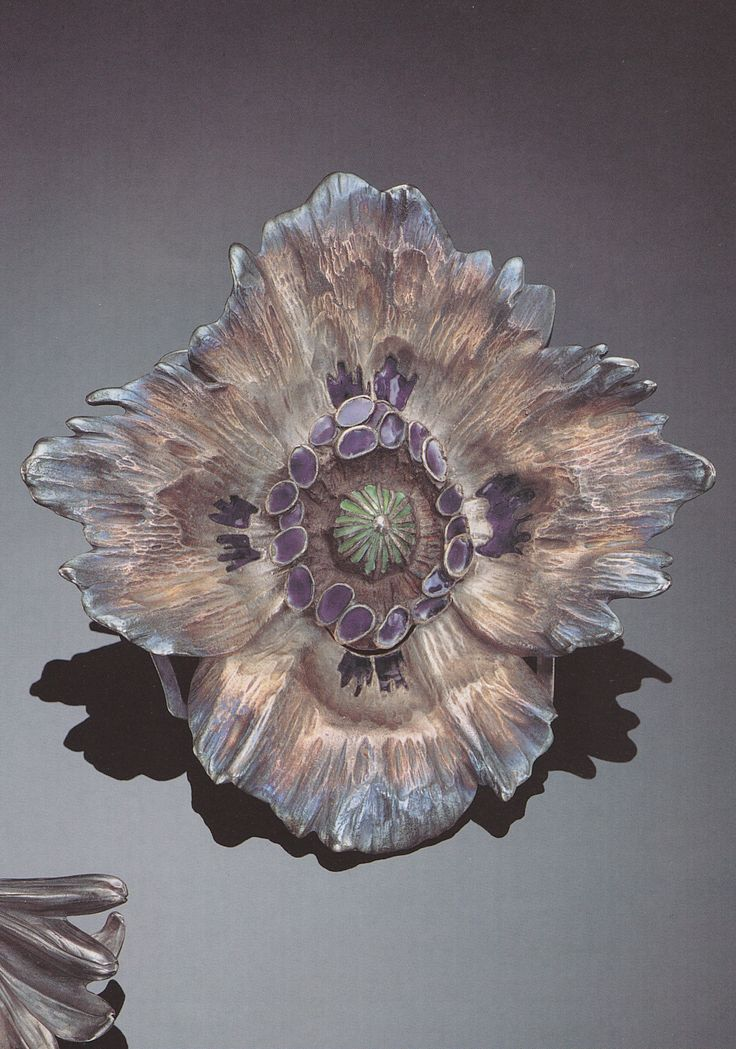 René Lalique - A FINE ART NOUVEAU ENAMELLED SILVER BELT BUCKLE, 1897-1898. In two parts: cast as a full blown poppy with undulating irregular outer petals, the stamen raised and enamelled in deep purple, the inner petals with traces of enamel, the pistil enamelled n grass green. Signed LALIQUE. 11cm. Source: Sotheby's Important Jewellery, Geneva, 20 January 1996.