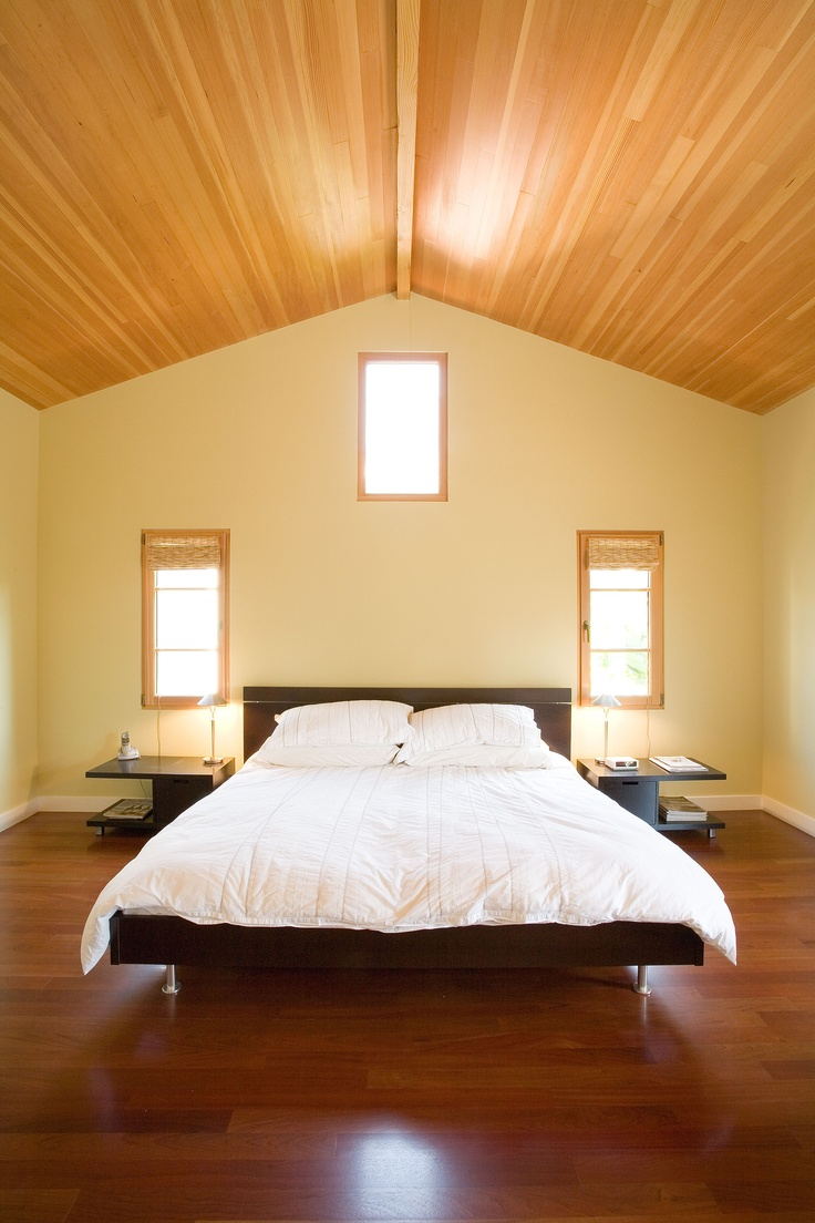 The master bedroom under a pitched, wood ceiling, is a lesson in simplicity and serenity.