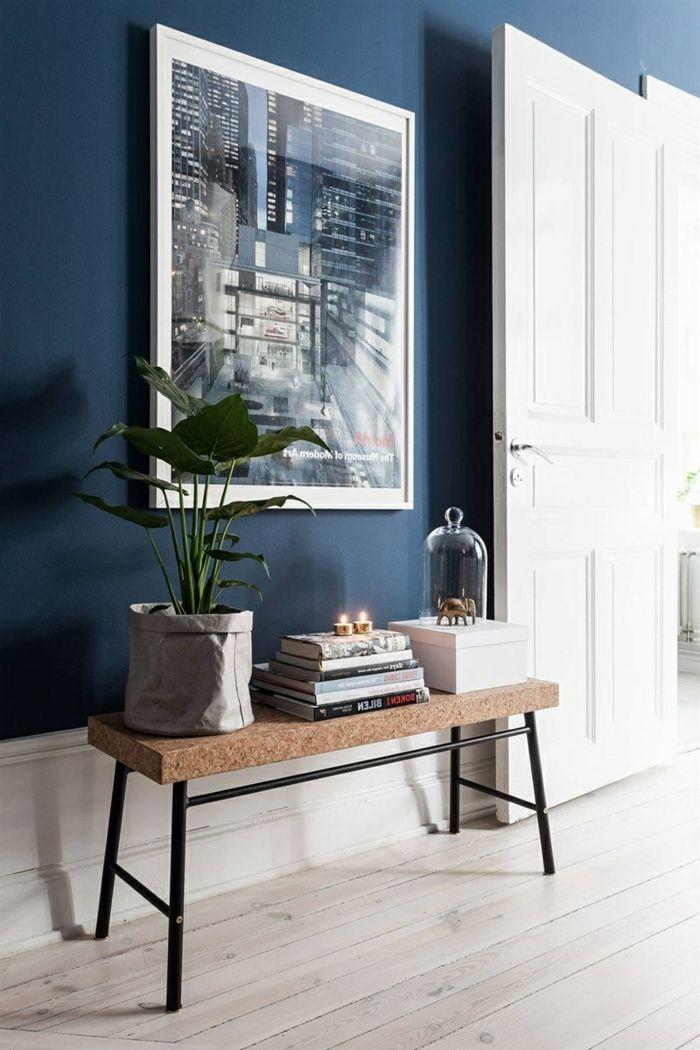 recibidores originales, recibidor con pared azul y cuadro grande, banco de corcho con planta verde y libros